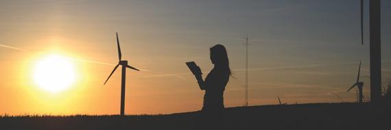 Een vrouw die iets bekijkt bij windmolens en een ondergaande zon.